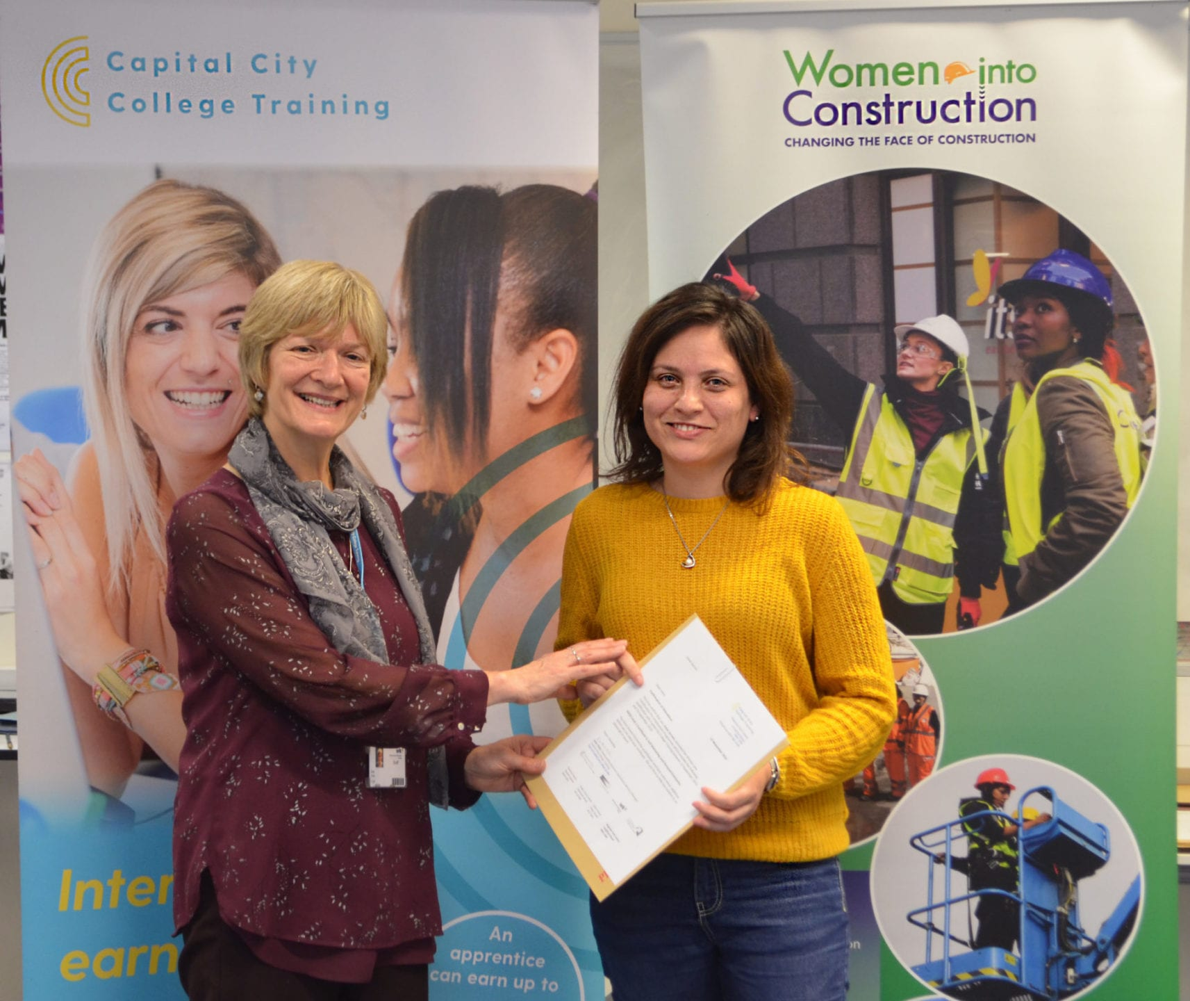 A graduate of the Women into Construction programme receives her completion certificate from Kate Child, Business Operations Manager at Capital City College Training